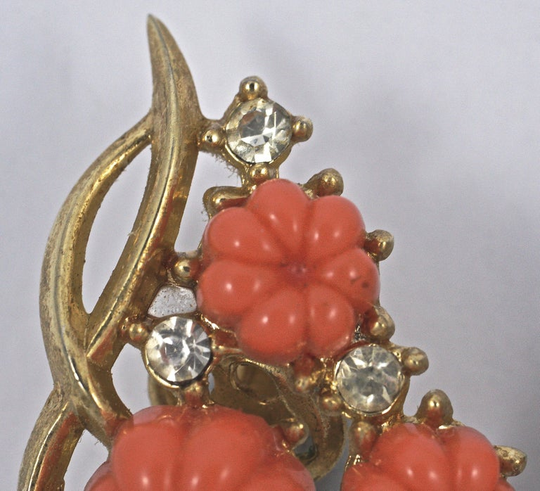 Beautiful Trifari gold plated fruit salad clip on earrings in an organic shape, featuring moulded coral glass flowers and clear rhinestones. Measuring length 3cm / 1.8 inches by width 2cm / .79 inch.   This is a lovely pair of older Trifari