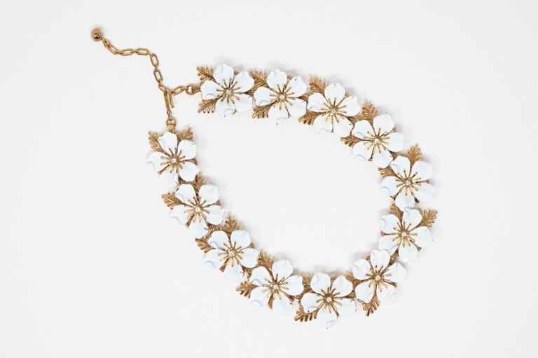 Gorgeous rare gold-plated and white enamel flower choker necklace with crystal rhinestone accents by Trifari, circa 1960s. Trifari is a highly collected costume jewelry brand, noted for its quality and intricate details. This mid-century modern
