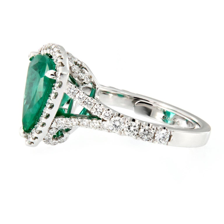 Modern and strikingly unique, this trillion cut emerald ring is sure to stand out. The center stone is 3.88 carat Zambian emerald beautifully accented with 1.0 cttw of VVS E RBC diamonds set in 18k white gold.   Ring Size 6.5.