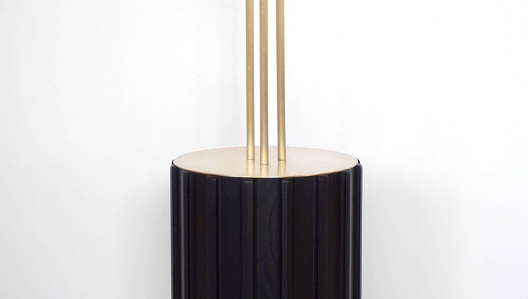 Trillium floor lamp is made of brass and blackened ashwood. Three rings sit at eye level, each with a light source hidden within, between two brass discs. The light seeps out from the discs and is bounced off the interior of the rings, with a soft