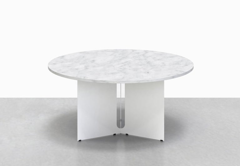 Our Trilo round table is polished but unpretentious. Choose between a solid walnut or variegated white marble top, anchored by a steel base with a playful geometrical cut-out detail.