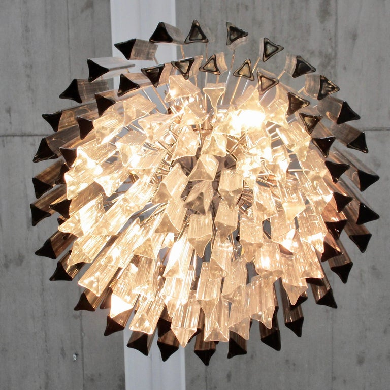 'TRILOBI' glass chandelier, Italy, Murano.  Glass chandelier with clear and smoke coloured 'Trilobi' glass made in Murano. Multi-tier glass chandelier with chromed plated metal frame.