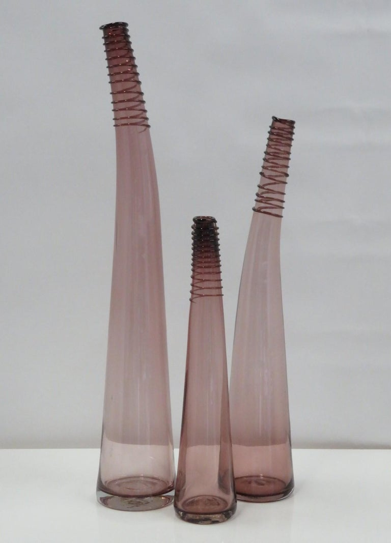 Blenko Set of 3 of Bent Spiral Neck Bottle Vases, in three heights, created by Don Shepherd in 1988. This designed makes its debut in the 1988 Blenko catalog and assigned number 8827 l/m/s depending on the height of the vessel. Beautiful purple