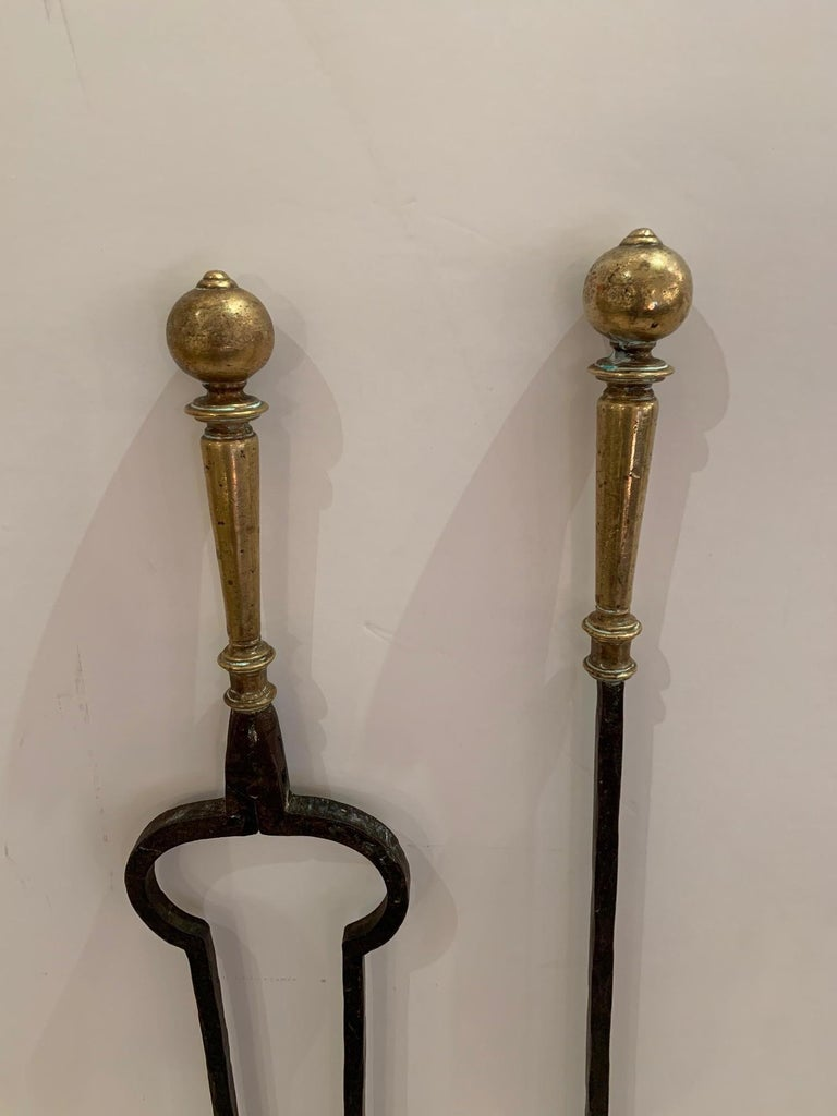 """A handsome set of black hand forged iron fireplace tools with brass handles. Measures: Fork 32.75"""" H x 4.25"""" W x 2"""" D Tongs 32"""" H x 4.75"""" W x 2.5"""" D Brush 26.75"""" H x 3"""" W 2.5"""" D."""