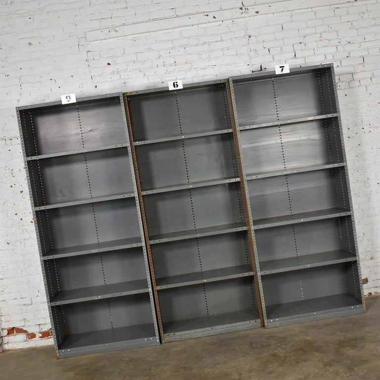 Awesome vintage industrial steel bookcase or shelving units. They are painted an industrial gray / green and have great age patina. All are in solid sturdy condition, but each have their own personality of dings, dents, rust and bare spots that