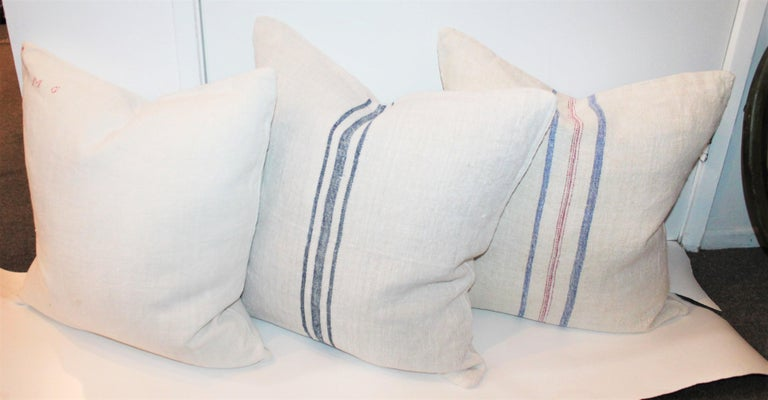 Hand selected 19th century linen made into a set of three pillows. This linen has been professionally laundered/cleaned and made with the best vintage linens found.  The blue and red striped linen pillow is a double sided with identical pattern on