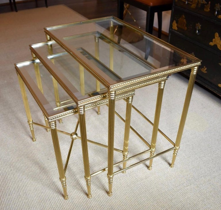 Set of 3 brass nesting tables in the manner of Maison Jansen crafted in France or Italy. Solid brass construction with beaded detail at tops it inset glass tops with mirrored edge detail. These are a larger scale set of nesting tables and the height