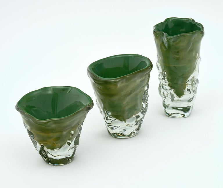 """Trio of """"martellato"""" Murano glass vases signed by glass blowing maestro Alberto Dona. This set has a beautiful green hue within layers of translucent glass and is blown using the """"massiccio martellato"""" or hammered technique. 23-carat gold flecks are"""