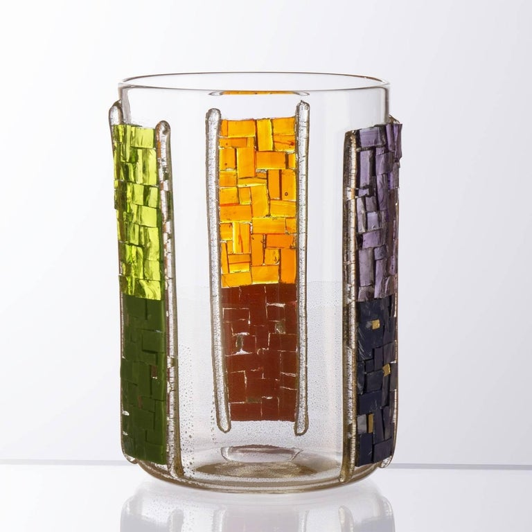 Part of the Tableware collection this colorful candle holder is made of Murano mouth-blown clear glass with three mosaic stripes in secondary colors: green, orange, and purple that have been applied