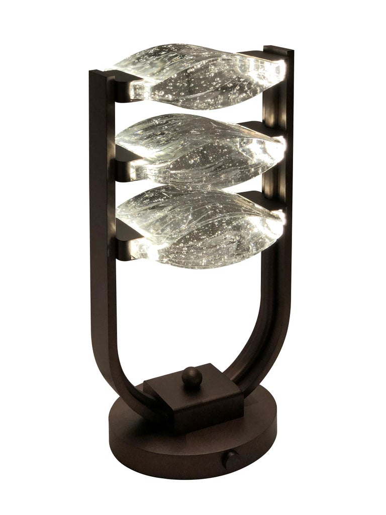 Other plugs are available by request.  Description: Brass Trio Table Lamp LED with Bubble Glass Color: Bronze Size: 22 x 11 x 36H cm Material: Bronze and Glass Collection: Mid Century Rhythm Plug: UK Plug Voltage: 220