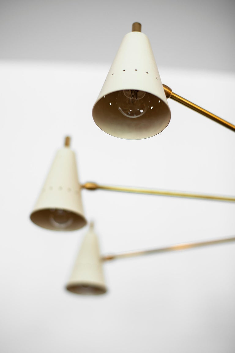 Architectural triple headed counterbalance ceiling pendant. Newly produced in Italy - 3 cantilevered small creamy white cones with perforated shades on one side and larger shade on alternate side. In the essence of Sarfatti. Unlacquered brass and