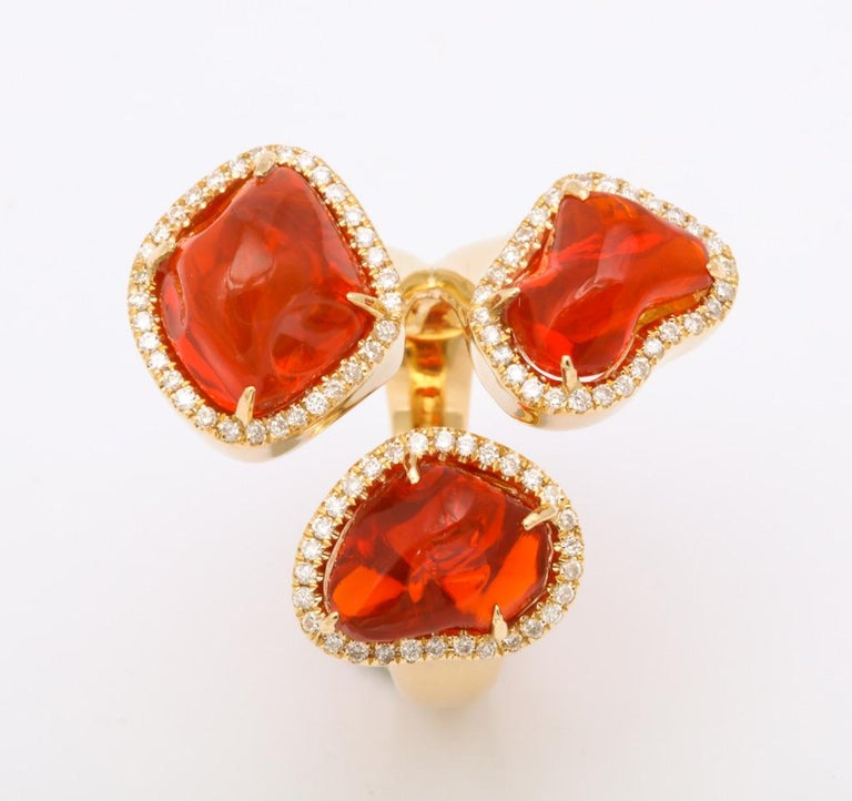 The triple stone ring is comprised of three baroque, free-form cut Mexican fire opals (3=7.21cts) each encircled with diamonds (0.36cts) and set in 18kt yellow gold.  A one of a kind, bright vivid orange show stopper.  Size 6 1/2  Fire opals
