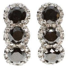 Triple Solitaire Black and White Diamond Clip Earrings in White Gold