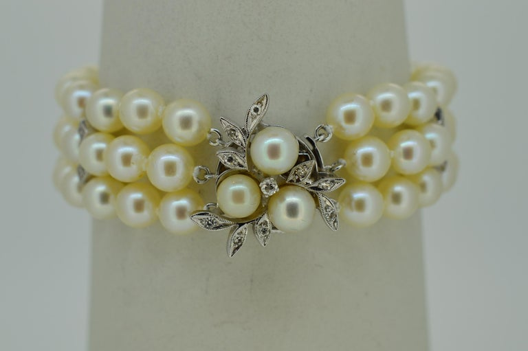 cc8471f30718d2 Triple Strand Fine Lustrous Akoya Pearl Bracelet with White Gold and  Diamond Floral Clasp. Three