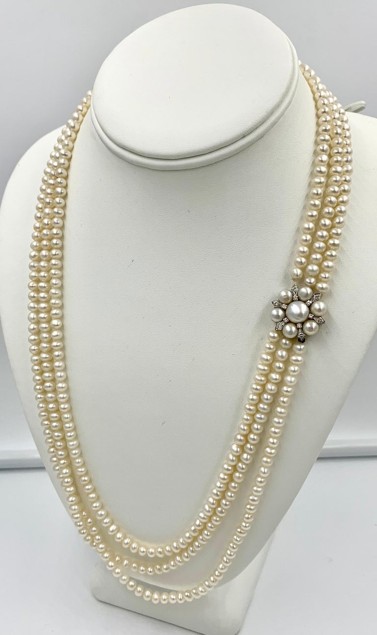 A gorgeous antique Triple Strand Pearl and Diamond Necklace in 14 Karat White Gold.  The Retro Hollywood Regency jewel is a stunner.  It has three rows of 5 mm luscious Pearls.  The Pearls are stunning with beautiful nacre and lustre.  The clasp is