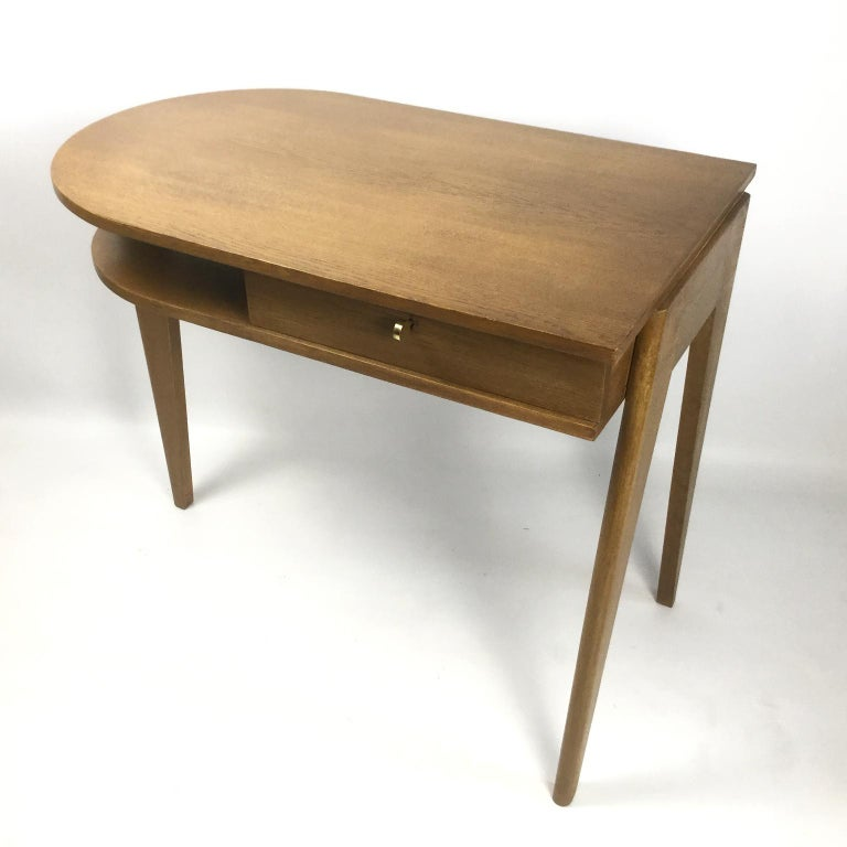 Oak desk with the rectangular top rounded to the right.  Opens on the front with a drawer and an open niche  The lock and key are in good working condition Tripod base with a flat post slightly protruding from the top. Postmodernism Movement
