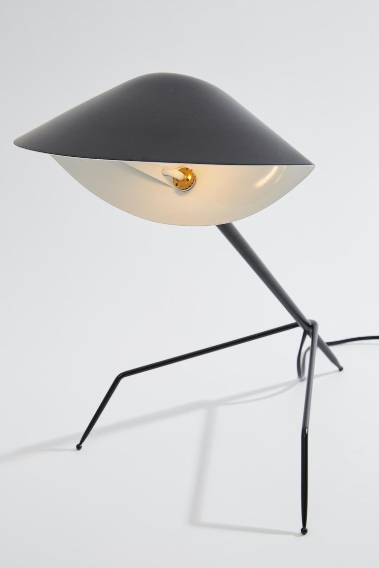 "Tripod desk lamp originally designed by Serge Mouille in 1954. This desk lamp is a licensed re-edition from the ""Black Shapes"" series currently manufactured by Editions Serge Mouille in France. The steel base has three legs and an aluminium"