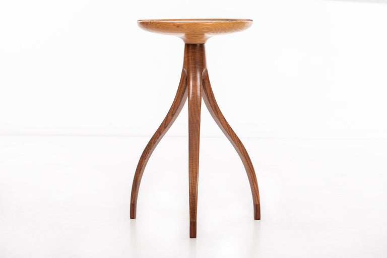 Slender scale high tripod table, solid carved bleached walnut lip edge top with ceramic design detail inset. Feet have darker tone wood accent.