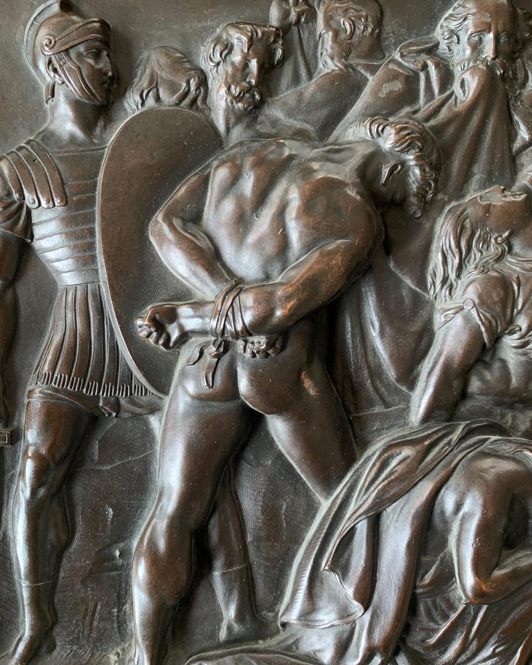 Beautifully detailed and masterfully cast and patinated, this bronze panel, probably from the late 19th or early 20th centuries, depicts a frieze of Roman soldiers at the end of battle, arrayed across the field with the forces they defeated either