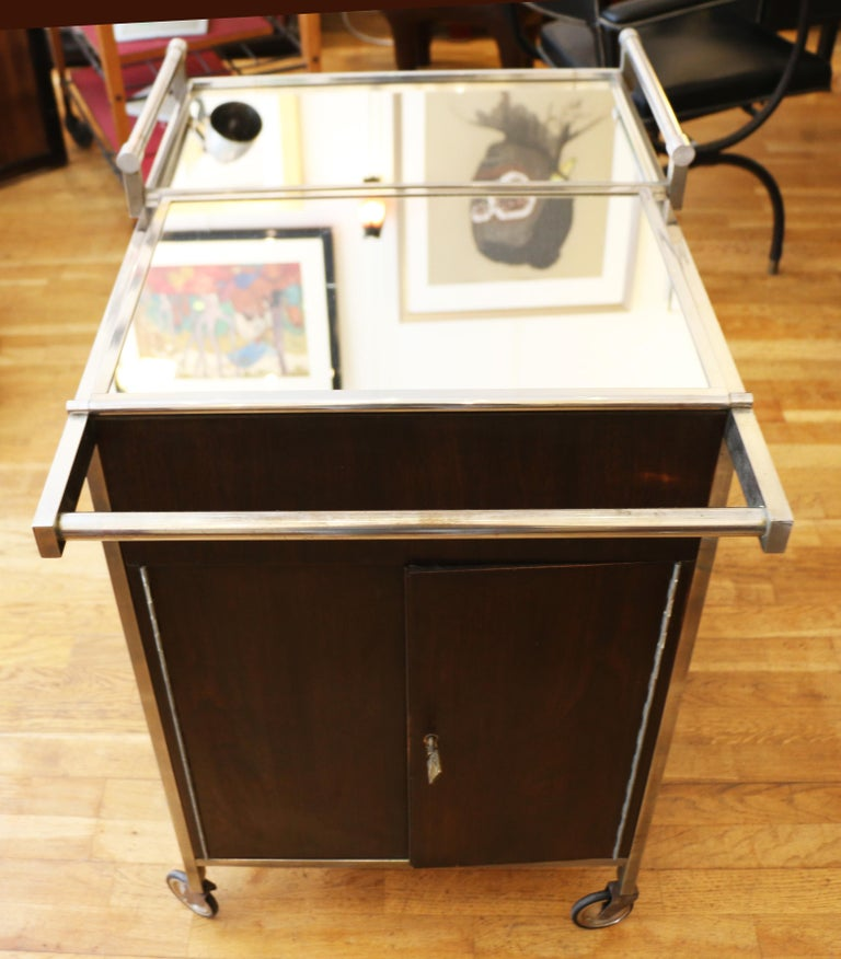 A trolley bar by Jacques Adnet (1900-1984). Chromed metal, aluminium and mahogany veneer structure, lower part fitted as a bar, ice cube box, the two upper trays are mobile. (Key is working but not original). 1930s.