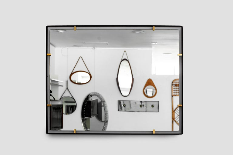 Iron frame and polished brass clasps support a floating rectangular mirror. Modeled after a vintage Italian design, newly produced at orange. Customizable sizes and finishes available.