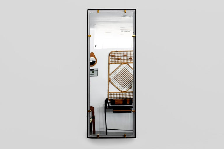Iron frame and polished brass clasps support a floating rectangular mirror.  Modeled after a vintage Italian design, newly produced at orange.  Customizable sizes and finishes available.  Measures: 18