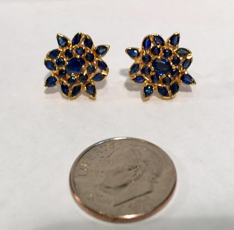 Elegantly proportioned and easy to wear 22 karat yellow gold estate earrings feature prong, tension and pave set oval, round, marquise and pear cut blue sapphires arranged in stylized snowflake or flower designs.  Posts feature screw backs for
