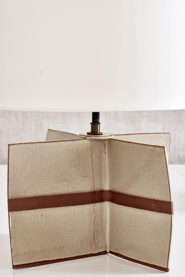 """Handmade stoneware slab construction. Lamps are individually crafted and one of a kind.  Ochre glaze with exposed central stripe. Antique brass fittings with braided black silk cord and off-white paper shade.  Measures: Base height 8.25"""" Base"""