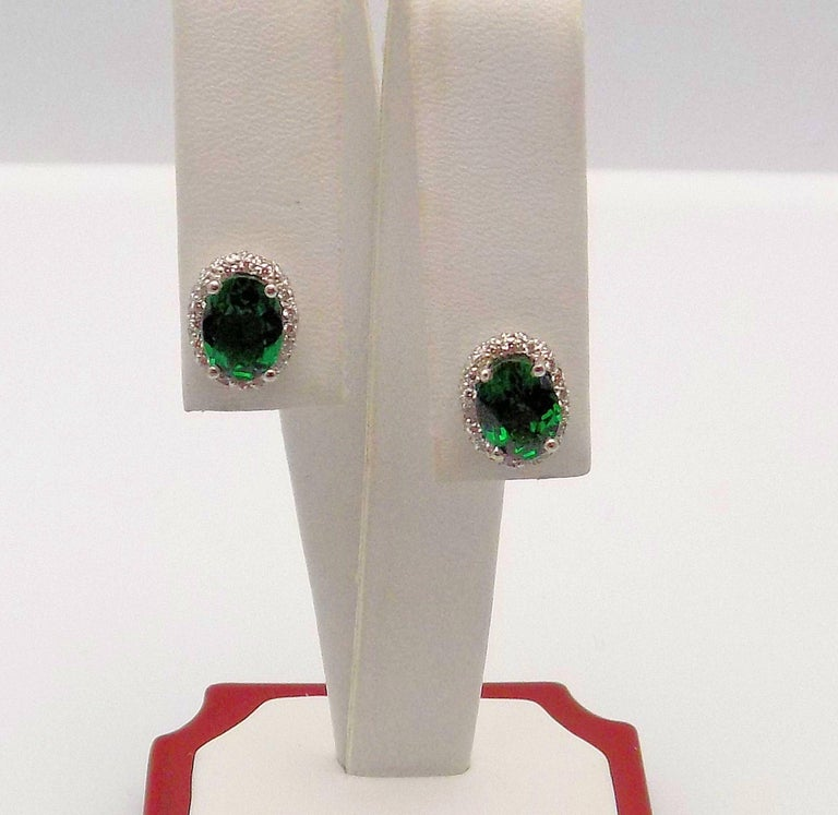Pair 14 Karat White Gold Stud Earrings Featuring 2 Oval Tsavorite Garnets 2.00 Carat Total Weight, 68 Round Brilliant Diamonds 0.35 Carat Total Weight, SI, H; 3.3 DWT or 5.13 Grams.