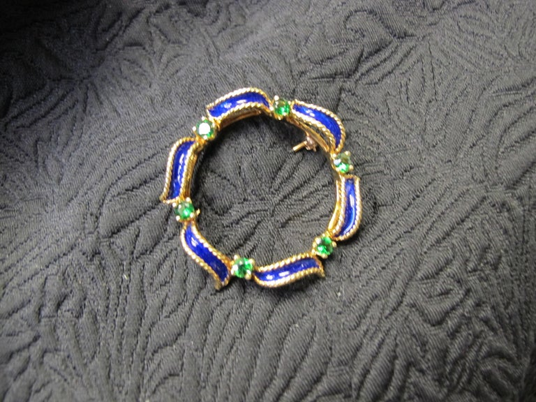 This classic circle pin has a beautiful combination of navy blue enamel and deep green garnets.  Six round tsavorite garnets weighing a total of .55 carats are set in the pin. It is made of 18k yellow gold. So pretty!!