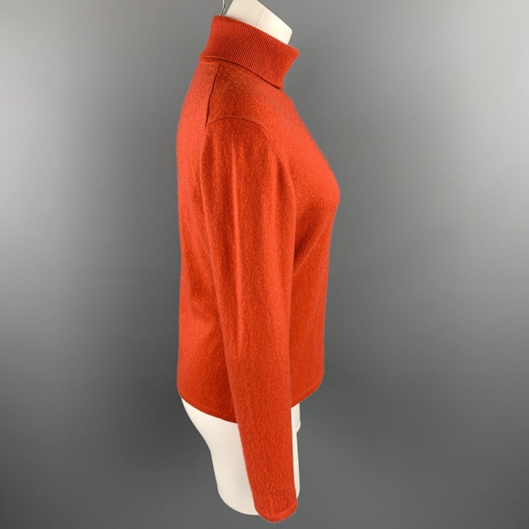 TSE sweater comes in a coral knitted cashmere featuring a turtleneck style.  Very Good Pre-Owned Condition. Marked: No size marked  Measurements:  Shoulder: 18 in.  Bust: 38 in.  Sleeve: 24 in.  Length: 22 in.   SKU: 92737 Category: Sweater  More