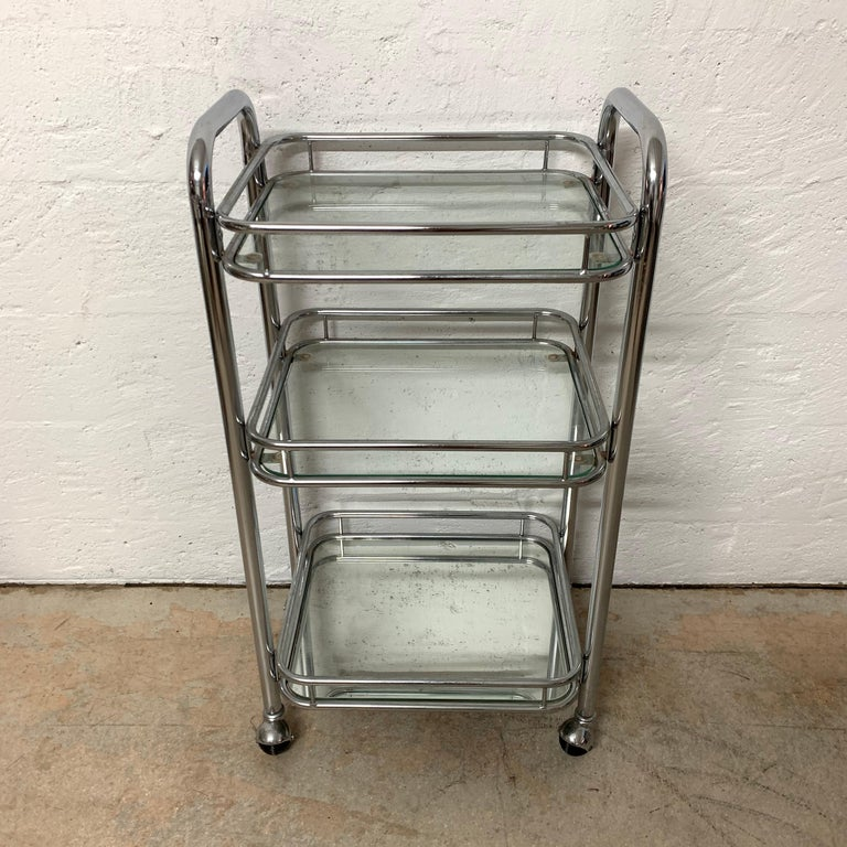 Art Deco style bar cart or trolley rendered in chrome-plated tubular steel with 4 wheels or castors for mobility and 2 glass shelves and a mirrored bottom shelf.