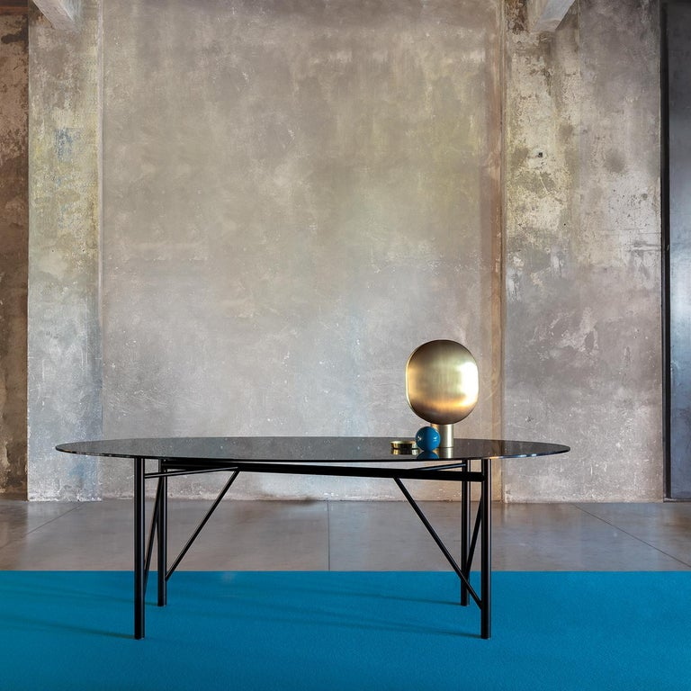On a refined metal base in a black powder coated finish, the Tubular oval dining table is topped with a gray glass top that allows the base to take center stage. The epitome of contemporary cool, the table is designed for minimalist spaces. The