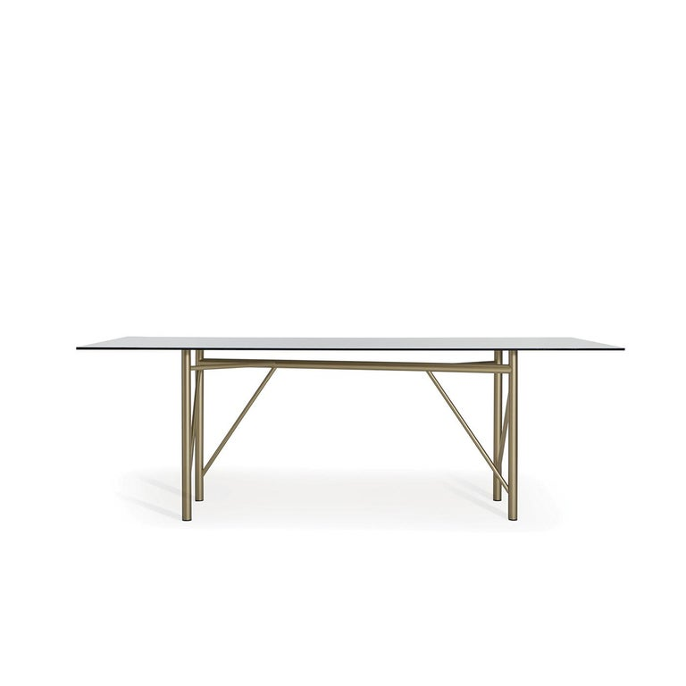 Treat your guests to ultimate contemporary luxury with the Tubular rectangular dining table. On a metal tube base with a brass powder-coated finish, the table is topped with a transparent gray tempered glass top that allows the base to be fully