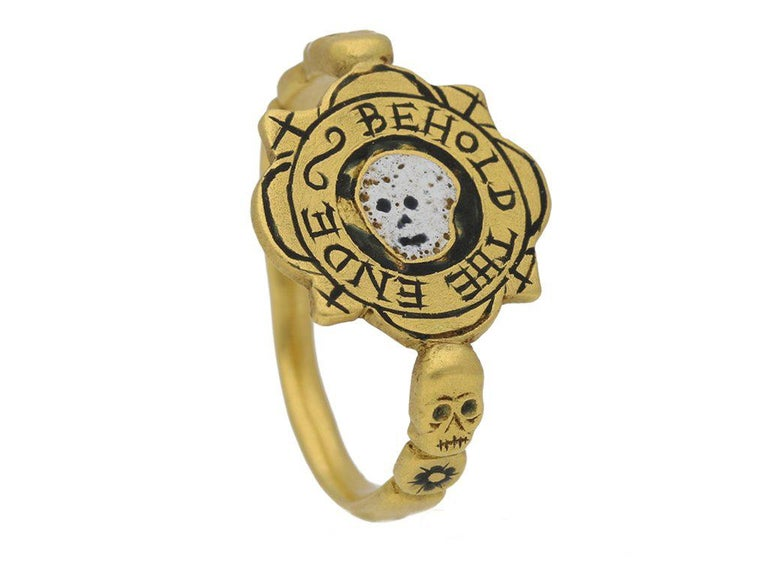 Tudor enameled 'BEHOLD THE ENDE' skull ring. Formed to centre with a irregular quartefoil bezel, featuring a horizontal white and black enameled skull encased in a circular black enameled background, surrounded by the inscription 'BEHOLD THE ENDE'