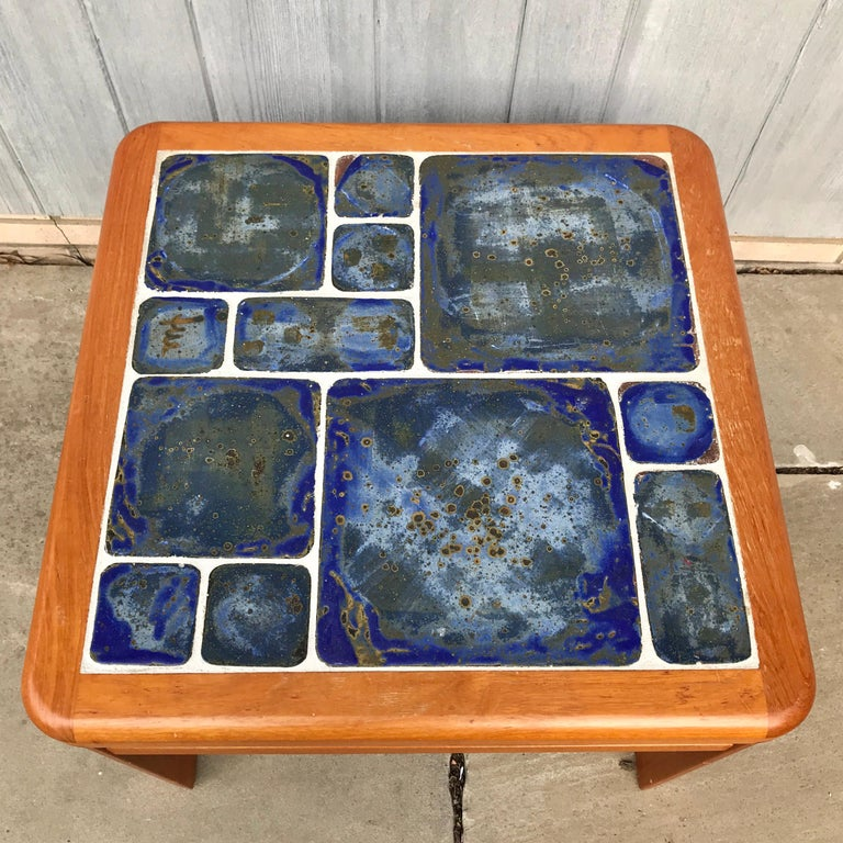 Gorgeous coffee or cocktail table by Tue Poulsen for Haslev of Denmark. Signed By the artist and also with manufacturer's label. From the 1960s. Beautiful hand painted blue green tiles on square frame. In good condition.