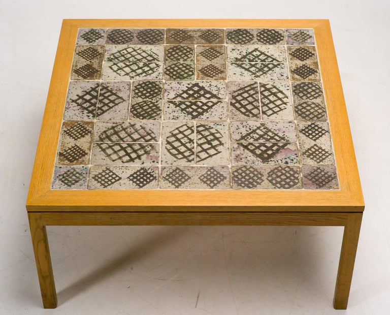 Square coffee table by Erik Wørts & Tue Poulsen with ceramic tile top laid inside an ash table frame.  The tiles are handcrafted by the Danish ceramicist Tue Poulsen.  One tile is signed