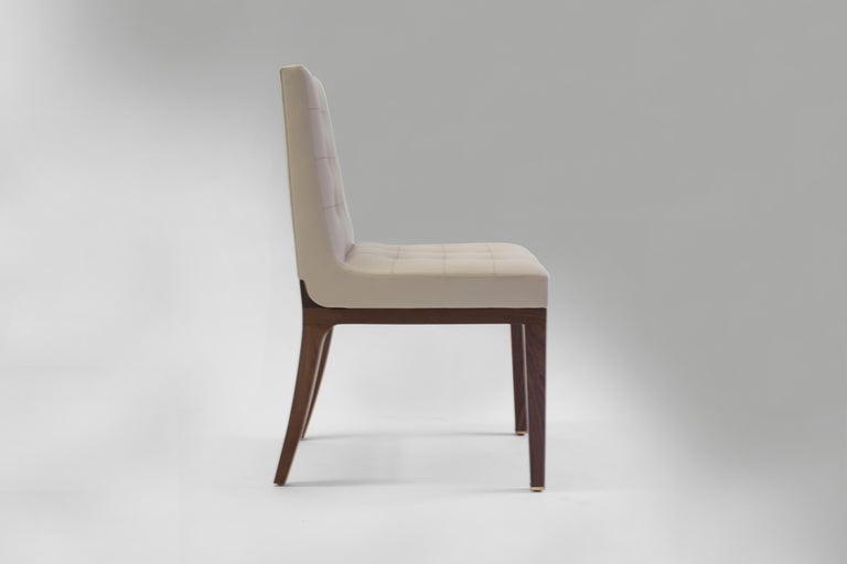 The Corbin side chair can be used as a dining chair, desk chair or an occasional chair, currently covered in tan leather with biscuit tufting on inside back with hand stitching in each tuft. Wood frame and legs made and finished in medium oak, also