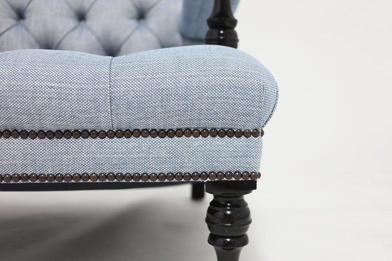 The Lewis club chair shown in blue linen fabric with tufted back and self covered buttons. All hair filled and stitched upholstery with hand carved dark mahogany wood legs and arm stretchers with special nailhead trim detail. Item is available