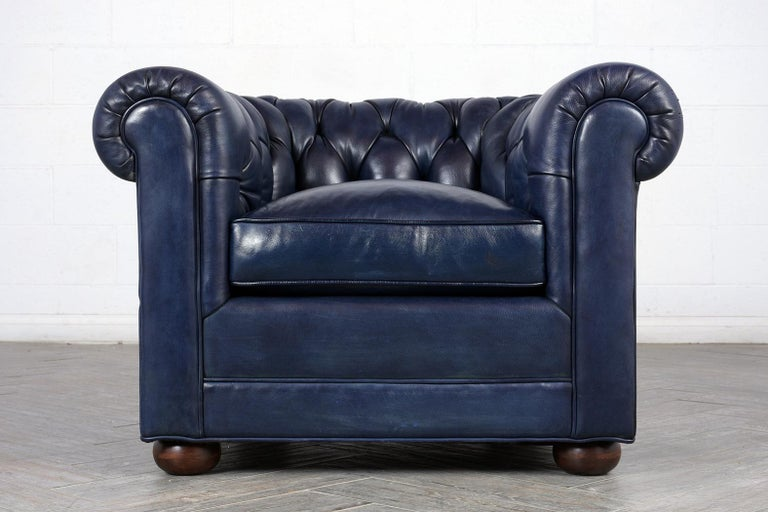 This English 1980s tufted leather Chesterfield-style club chair is upholstered in a navy blue color leather with tufted detail along the scrolled arms and back. The chair is in excellent condition with a single comfortable seat cushion filled with