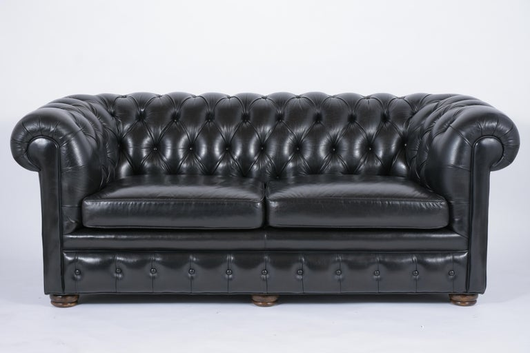 This 1970s leather chesterfield sofa has been professionally restored, comes with its original leather dyed in a very dark green color, and newly polished patina finish. The sofa features a tufted design on the arms & backrest, single piping details