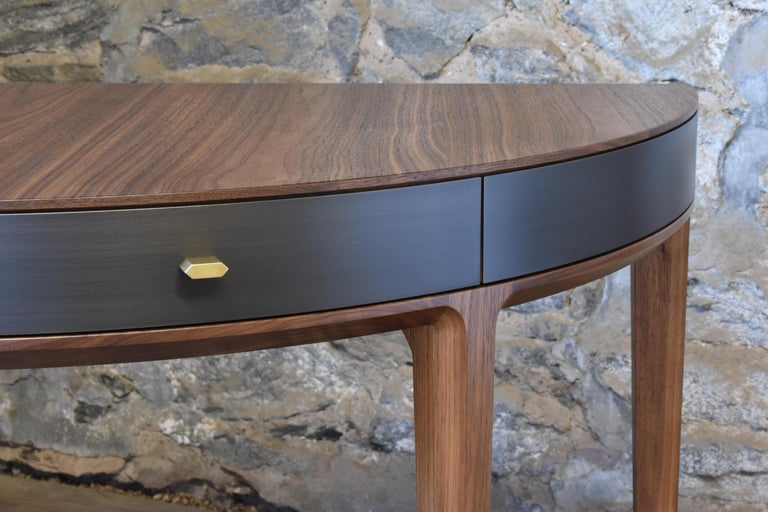 Shown in oiled walnut and gunmetal steel with burnished bronze hardware, the Tulare demilune desk features two solid wood drawers, custom made hardware and hand applied finishes. Dimensions (as pictured): 48