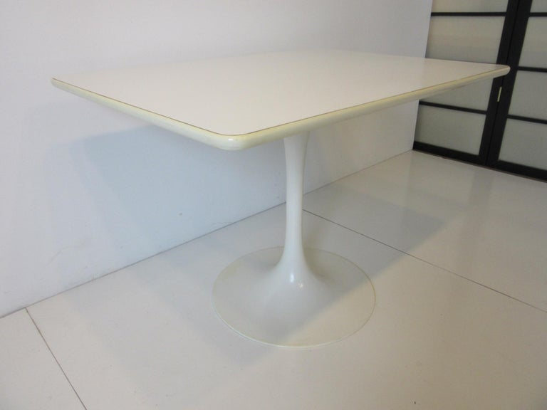 A hard to find rectangle tulip based cafe or smaller dining table with white laminate top, rubber edge strip and metal base. Manufactured by the Burke Furniture company, the perfect size for your eat in kitchen or a smaller dining space.