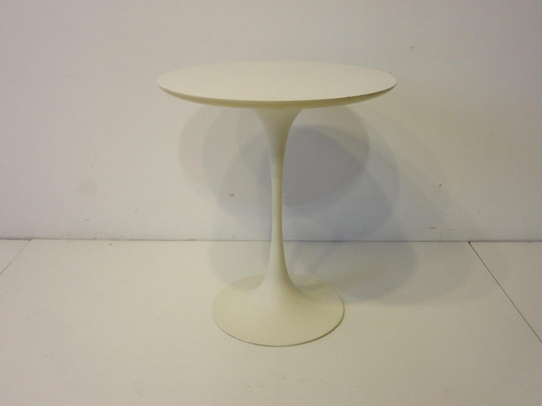 A tulip based pedestal side table with a satin white cast metal base and matching round laminate top designed in the manner of Eero Saarinen and Knoll, manufactured by the Burke Furniture Company.