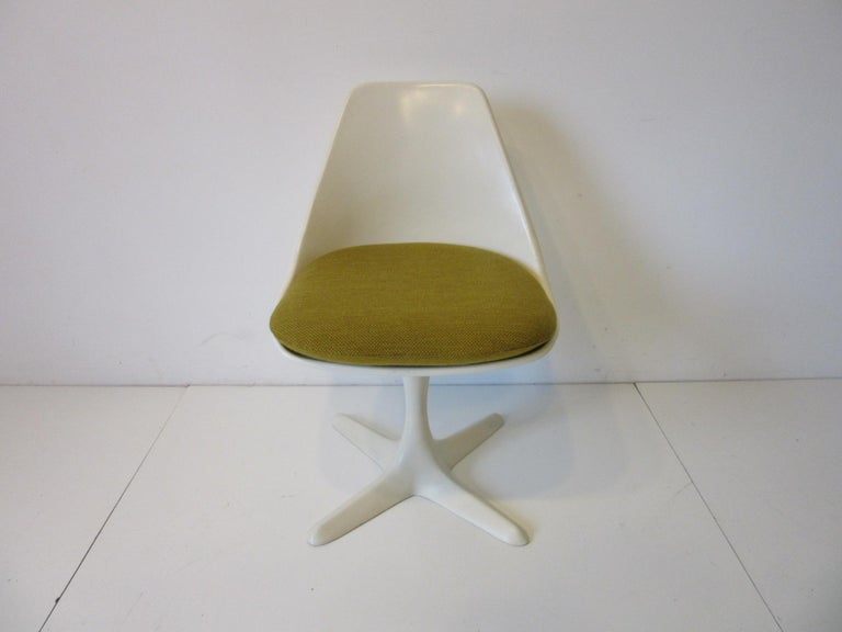 A set of four Saarinen styled non swiveling dining chairs in molded fiberglass with coated metal star bases and upholstered seat pads. The seat pads are in the original vintage harvest gold woven fabric from the period, the chairs and cushion retain