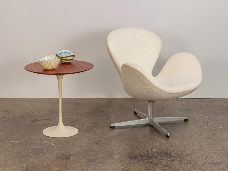Iconic Eero Saarinen tulip side table in walnut for Knoll. This petite version of the large Saarinen Tulip dining table echoes the organic, drop of liquid form. Despite the size, this side table maintains it's center of gravity; substantial weight