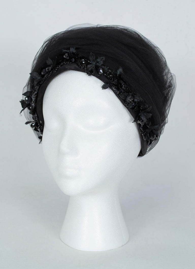 Not for the faint of heart, this frothy cocktail hat will add inches to your height and ensure you leave a memorable impression. Dangling faceted beads around the bottom edge add subtle sparkle and frame the face, while yards of tulle create a