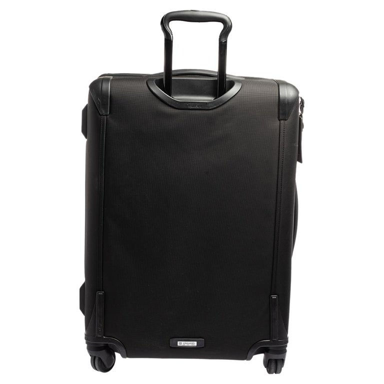 This Alpha 2 luggage bag is designed by TUMI in a black shade. This 4 wheeled luggage case features a big and one small zipper compartment with a brand logo at the front. Crafted from nylon, this luxury opens to a wide nylon-lined interior with
