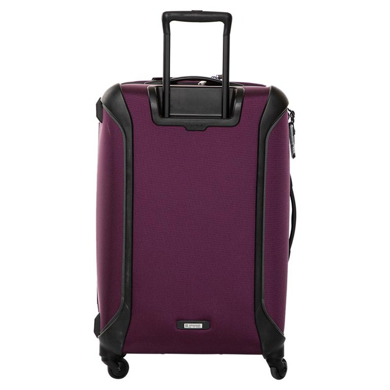 This Trip Packing Case Luggage bag from TUMI is made from purple nylon. Equipped with four wheels that offer unrestrained movement, the bag has a top carry handle along with zippers to ensure security. It boasts a nylon-lined spacious interior that