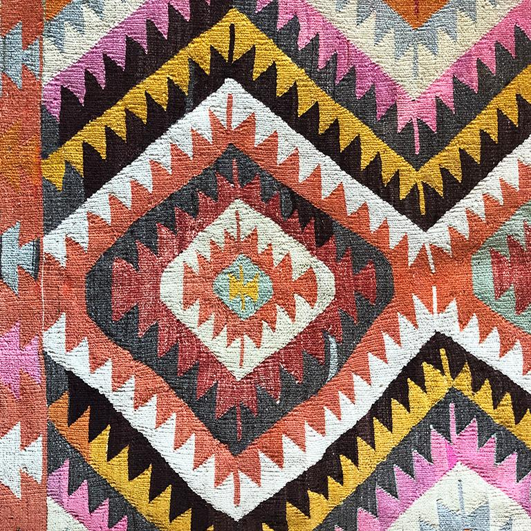 Colorful geometric Kilim rug from Turkey. Great for by a bed, in a nursery, front door or foyer. Colors in pink, yellow, black, orange, red white.